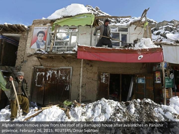 Afghan men remove snow from the roof of a damaged house after avalanches in Panjshir province, February 26, 2015. REUTERS/Omar Sobhani