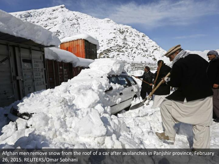 Afghan men remove snow from the roof of a car after avalanches in Panjshir province, February 26, 2015. REUTERS/Omar Sobhani