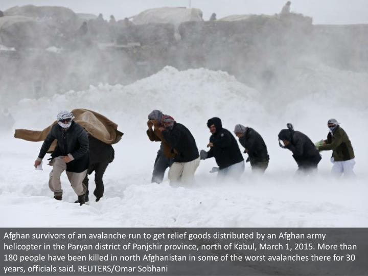Afghan survivors of an avalanche run to get relief goods distributed by an Afghan army helicopter in...