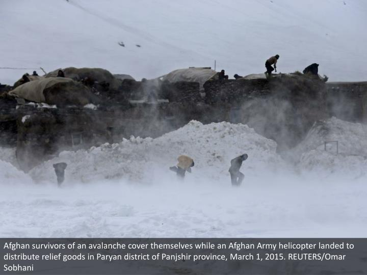Afghan survivors of an avalanche cover themselves while an Afghan Army helicopter landed to distribute relief goods in Paryan district of Panjshir province, March 1, 2015. REUTERS/Omar Sobhani