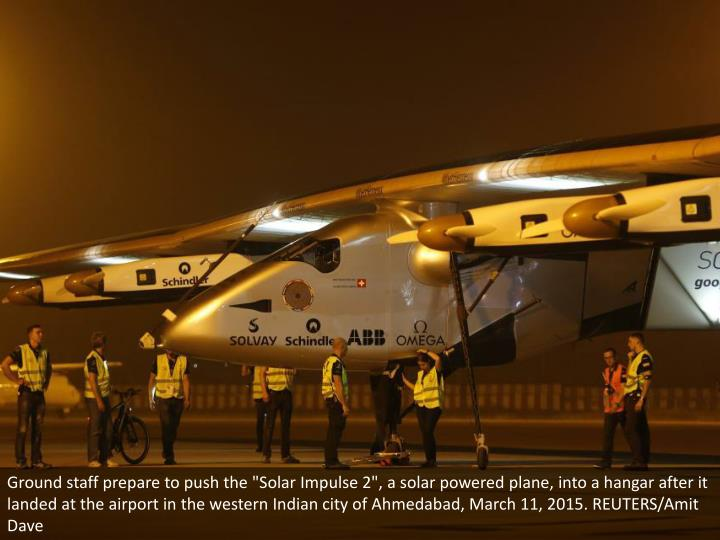 "Ground staff prepare to push the ""Solar Impulse 2"", a solar powered plane, into a hangar after it landed at the airport in the western Indian city of Ahmedabad, March 11, 2015. REUTERS/Amit Dave"