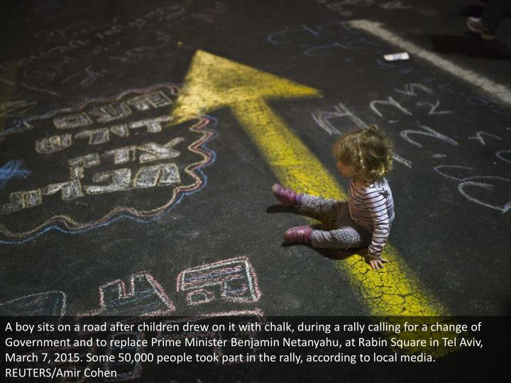A boy sits on a road after children drew on it with chalk, during a rally calling for a change of Government and to replace Prime Minister Benjamin Netanyahu, at Rabin Square in Tel Aviv, March 7, 2015. Some 50,000 people took part in the rally, according to local media. REUTERS/Amir Cohen