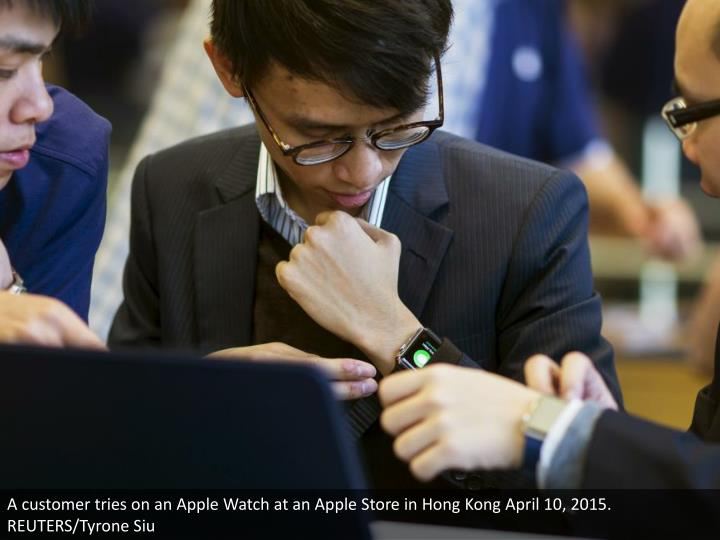 A customer tries on an Apple Watch at an Apple Store in Hong Kong April 10, 2015. REUTERS/Tyrone Siu