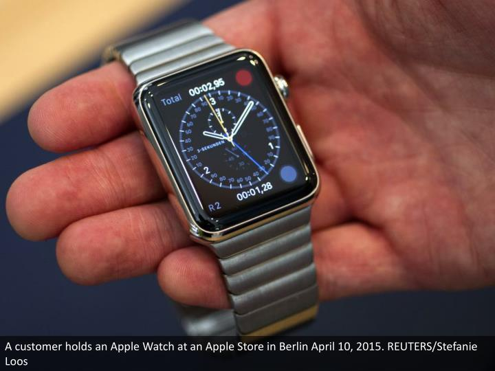 A customer holds an Apple Watch at an Apple Store in Berlin April 10, 2015. REUTERS/Stefanie Loos