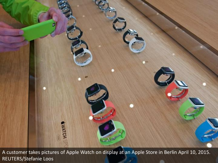 A customer takes pictures of Apple Watch on display at an Apple Store in Berlin April 10, 2015. REUTERS/Stefanie Loos