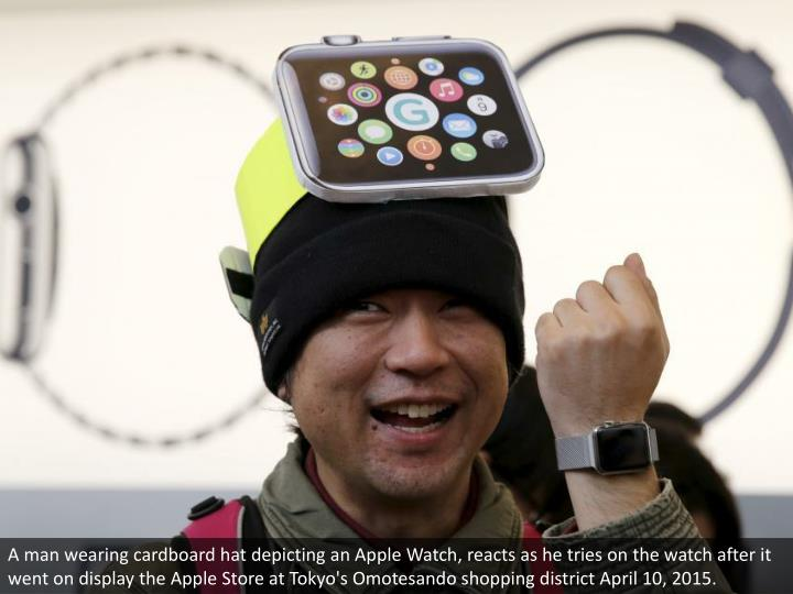 A man wearing cardboard hat depicting an Apple Watch, reacts as he tries on the watch after it went ...