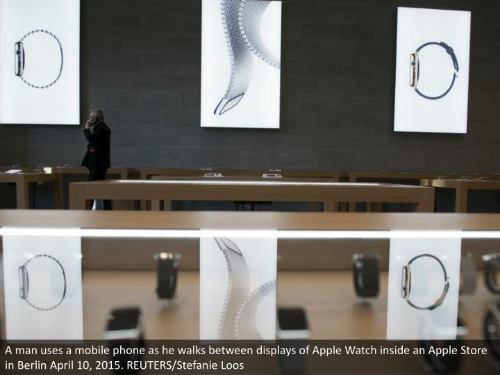 A man uses a mobile phone as he walks between displays of Apple Watch inside an Apple Store in Berlin April 10, 2015. REUTERS/Stefanie Loos