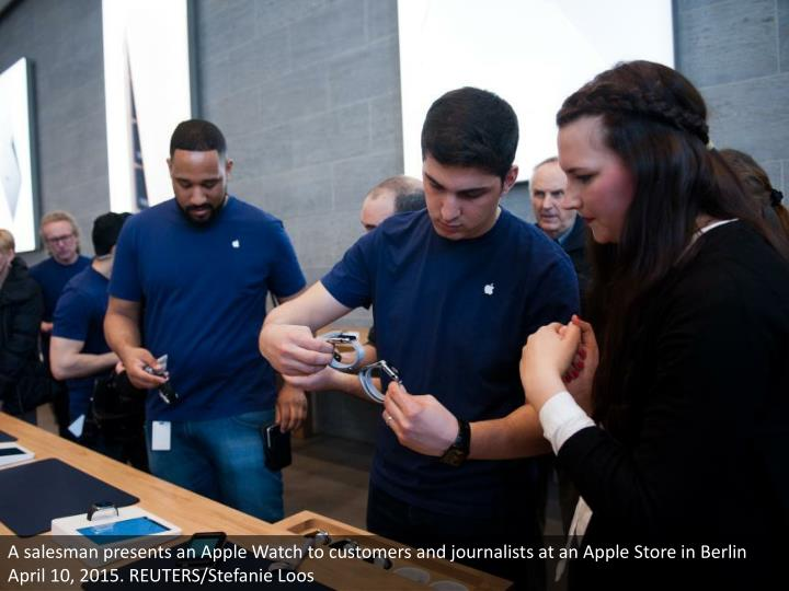 A salesman presents an Apple Watch to customers and journalists at an Apple Store in Berlin April 10, 2015. REUTERS/Stefanie Loos