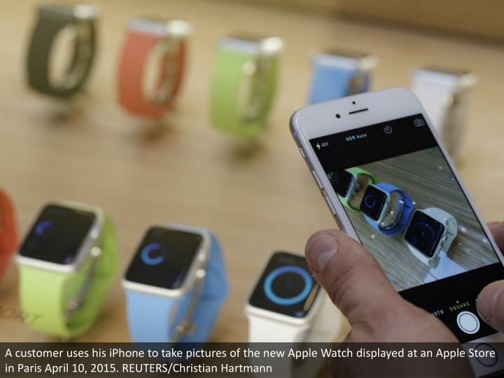 A customer uses his iPhone to take pictures of the new Apple Watch displayed at an Apple Store in Paris April 10, 2015. REUTERS/Christian Hartmann