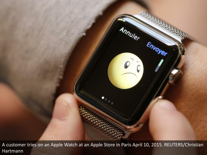 A customer tries on an Apple Watch at an Apple Store in Paris April 10, 2015. REUTERS/Christian Hartmann