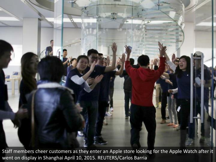 Staff members cheer customers as they enter an Apple store looking for the Apple Watch after it went on display in Shanghai April 10, 2015. REUTERS/Carlos Barria