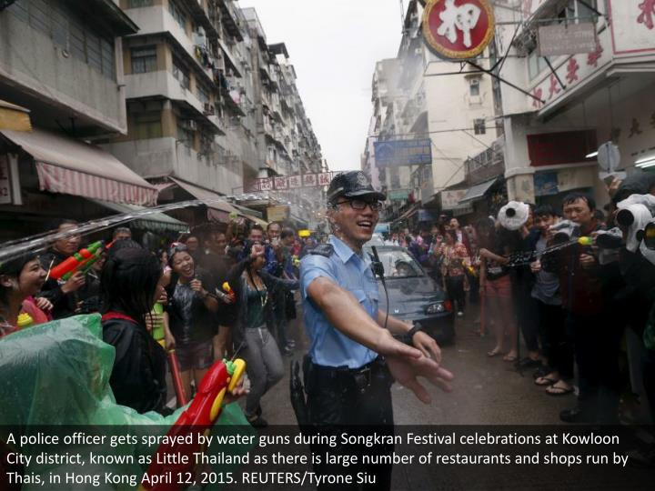 A police officer gets sprayed by water guns during Songkran Festival celebrations at Kowloon City district, known as Little Thailand as there is large number of restaurants and shops run by Thais, in Hong Kong April 12, 2015. REUTERS/Tyrone Siu
