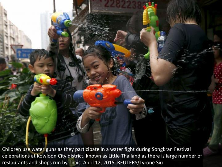 Children use water guns as they participate in a water fight during Songkran Festival celebrations at Kowloon City district, known as Little Thailand as there is large number of restaurants and shops run by Thais, April 12, 2015. REUTERS/Tyrone Siu