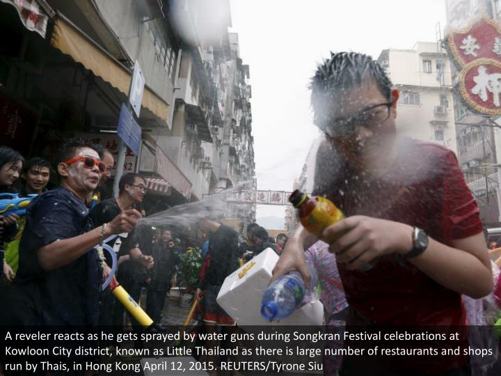 A reveler reacts as he gets sprayed by water guns during Songkran Festival celebrations at Kowloon City district, known as Little Thailand as there is large number of restaurants and shops run by Thais, in Hong Kong April 12, 2015. REUTERS/Tyrone Siu