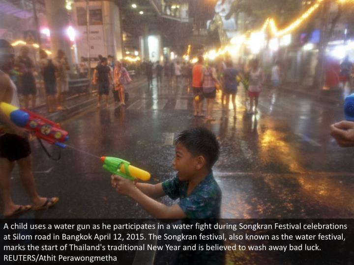 A child uses a water gun as he participates in a water fight during Songkran Festival celebrations at Silom road in Bangkok April 12, 2015. The Songkran festival, also known as the water festival, marks the start of Thailand's traditional New Year and is believed to wash away bad luck. REUTERS/Athit Perawongmetha