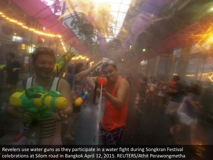 Revelers use water guns as they participate in a water fight during Songkran Festival celebrations at Silom road in Bangkok April 12, 2015. REUTERS/Athit Perawongmetha