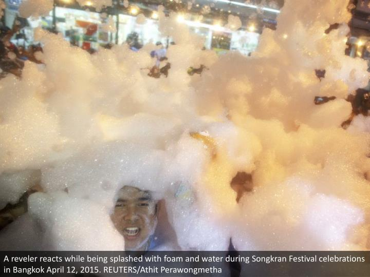 A reveler reacts while being splashed with foam and water during Songkran Festival celebrations in Bangkok April 12, 2015. REUTERS/Athit Perawongmetha