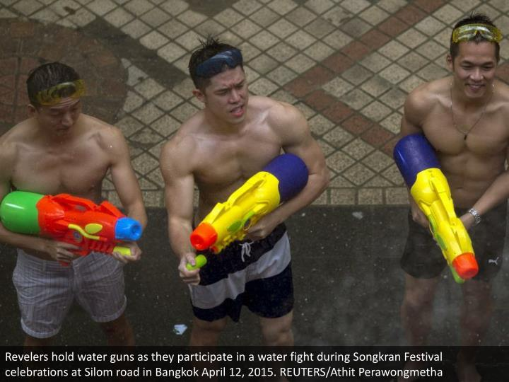 Revelers hold water guns as they participate in a water fight during Songkran Festival celebrations at Silom road in Bangkok April 12, 2015. REUTERS/Athit Perawongmetha