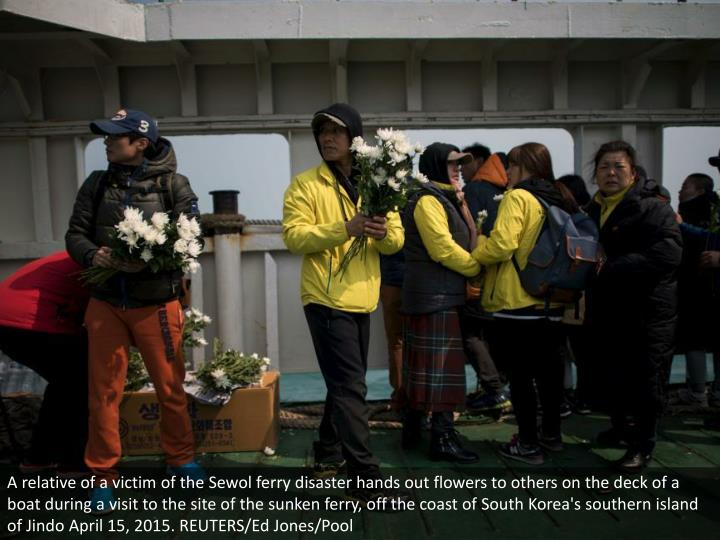 A relative of a victim of the Sewol ferry disaster hands out flowers to others on the deck of a boat during a visit to the site of the sunken ferry, off the coast of South Korea's southern island of Jindo April 15, 2015. REUTERS/Ed Jones/Pool