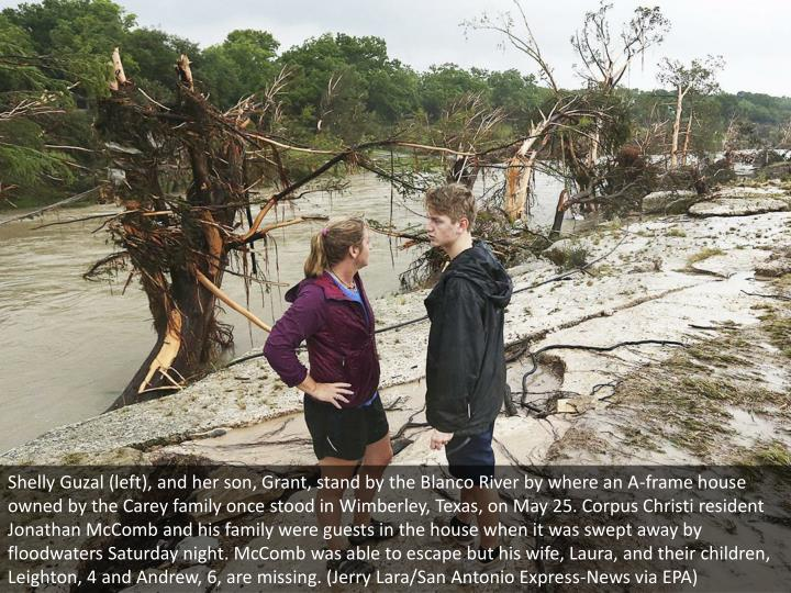 Shelly Guzal (left), and her son, Grant, stand by the Blanco River by where an A-frame house owned by the Carey family once stood in Wimberley, Texas, on May 25. Corpus Christi resident Jonathan McComb and his family were guests in the house when it was swept away by floodwaters Saturday night. McComb was able to escape but his wife, Laura, and their children, Leighton, 4 and Andrew, 6, are missing. (Jerry Lara/San Antonio Express-News via EPA)