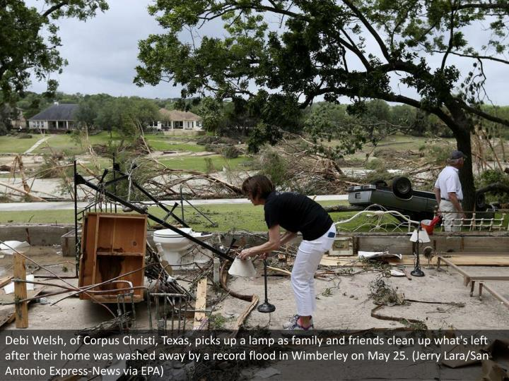 Debi Welsh, of Corpus Christi, Texas, picks up a lamp as family and friends clean up what's left after their home was washed away by a record flood in Wimberley on May 25. (Jerry Lara/San Antonio Express-News via EPA)