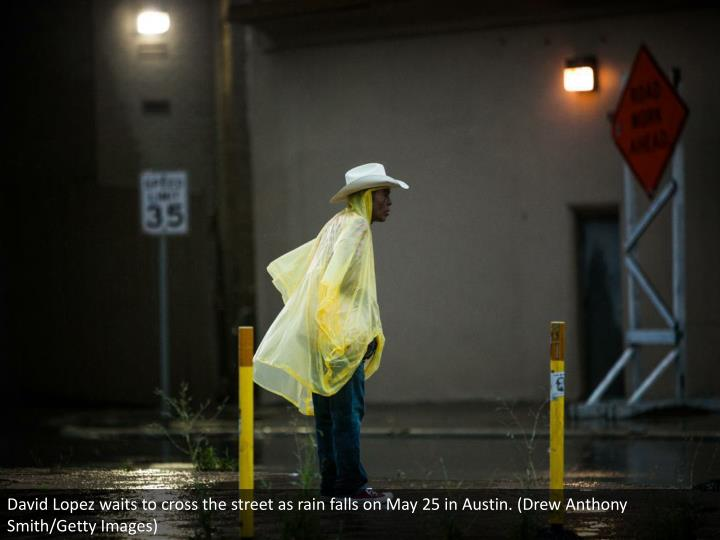 David Lopez waits to cross the street as rain falls on May 25 in Austin. (Drew Anthony Smith/Getty Images)