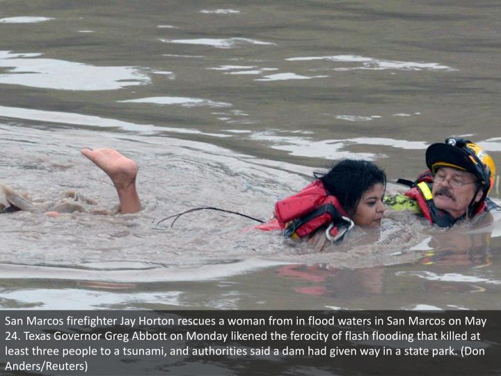 San Marcos firefighter Jay Horton rescues a woman from in flood waters in San Marcos on May 24. Texa...