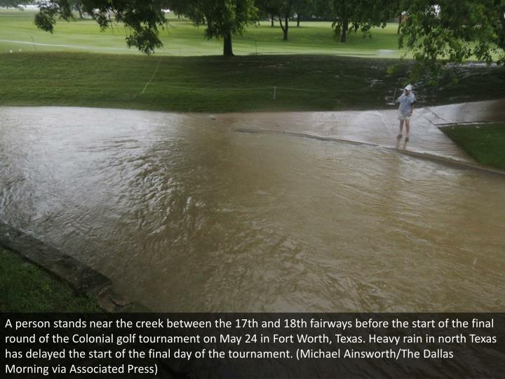 A person stands near the creek between the 17th and 18th fairways before the start of the final round of the Colonial golf tournament on May 24 in Fort Worth, Texas. Heavy rain in north Texas has delayed the start of the final day of the tournament. (Michael Ainsworth/The Dallas Morning via Associated Press)