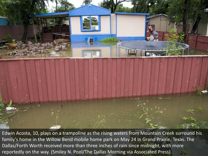 Edwin Acosta, 10, plays on a trampoline as the rising waters from Mountain Creek surround his family's home in the Willow Bend mobile home park on May 24 in Grand Prairie, Texas. The Dallas/Forth Worth received more than three inches of rain since midnight, with more reportedly on the way. (Smiley N. Pool/The Dallas Morning via Associated Press)