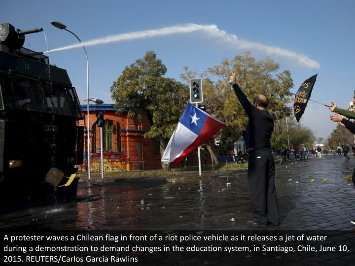 A protester waves a Chilean flag in front of a riot police vehicle as it releases a jet of water during a demonstration to demand changes in the education system, in Santiago, Chile, June 10, 2015. REUTERS/Carlos Garcia Rawlins