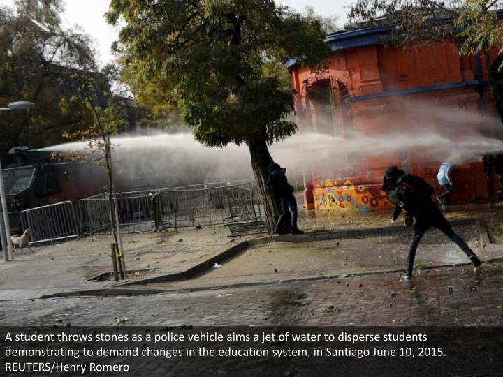 A student throws stones as a police vehicle aims a jet of water to disperse students demonstrating to demand changes in the education system, in Santiago June 10, 2015. REUTERS/Henry Romero