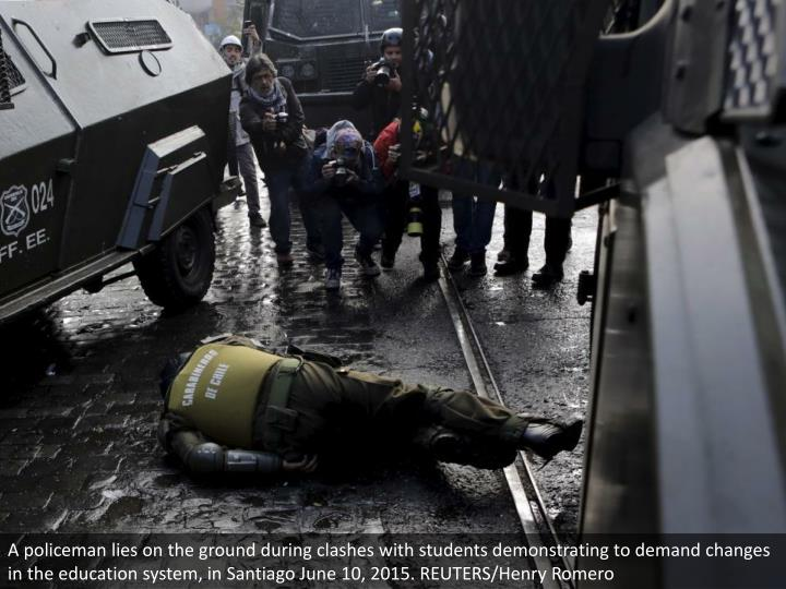 A policeman lies on the ground during clashes with students demonstrating to demand changes in the education system, in Santiago June 10, 2015. REUTERS/Henry Romero