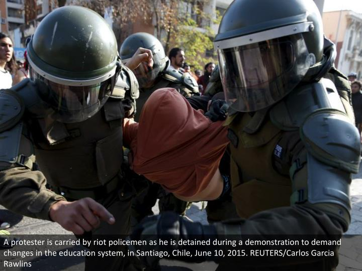 A protester is carried by riot policemen as he is detained during a demonstration to demand changes in the education system, in Santiago, Chile, June 10, 2015. REUTERS/Carlos Garcia Rawlins