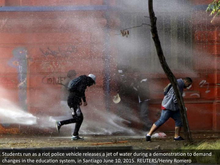 Students run as a riot police vehicle releases a jet of water during a demonstration to demand changes in the education system, in Santiago June 10, 2015. REUTERS/Henry Romero