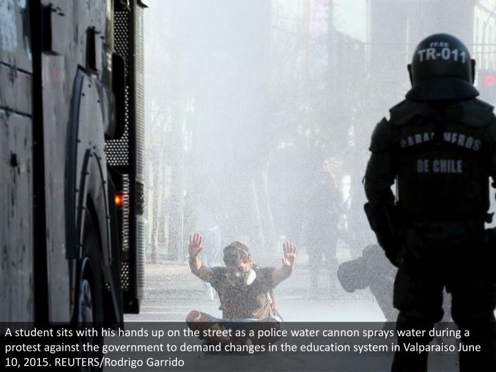 A student sits with his hands up on the street as a police water cannon sprays water during a protest against the government to demand changes in the education system in Valparaiso June 10, 2015. REUTERS/Rodrigo Garrido