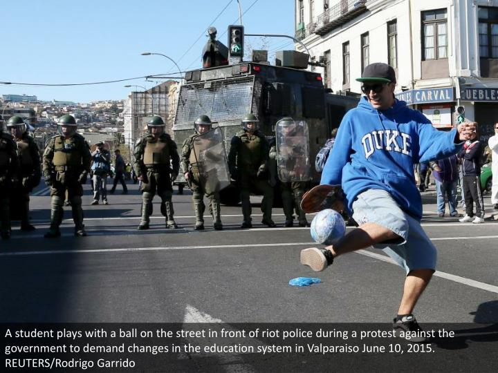A student plays with a ball on the street in front of riot police during a protest against the government to demand changes in the education system in Valparaiso June 10, 2015. REUTERS/Rodrigo Garrido