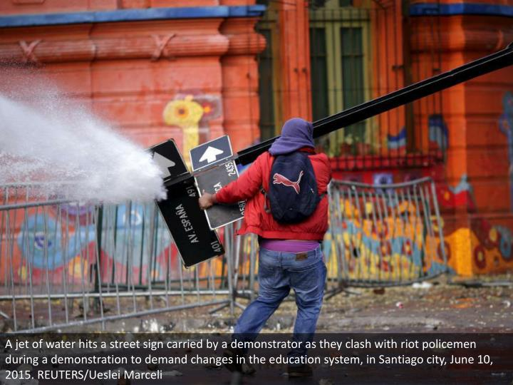 A jet of water hits a street sign carried by a demonstrator as they clash with riot policemen during a demonstration to demand changes in the education system, in Santiago city, June 10, 2015. REUTERS/Ueslei Marceli