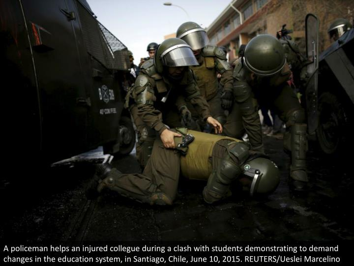A policeman helps an injured collegue during a clash with students demonstrating to demand changes in the education system, in Santiago, Chile, June 10, 2015. REUTERS/Ueslei Marcelino