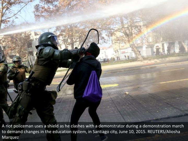 A riot policeman uses a shield as he clashes with a demonstrator during a demonstration march to demand changes in the education system, in Santiago city, June 10, 2015. REUTERS/Aliosha Marquez