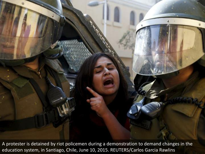 A protester is detained by riot policemen during a demonstration to demand changes in the education system, in Santiago, Chile, June 10, 2015. REUTERS/Carlos Garcia Rawlins