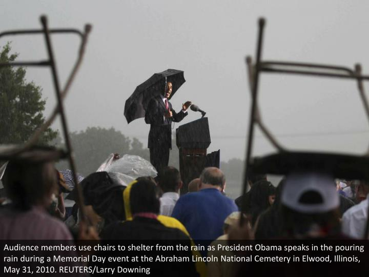 Audience members use chairs to shelter from the rain as President Obama speaks in the pouring rain during a Memorial Day event at the Abraham Lincoln National Cemetery in Elwood, Illinois, May 31, 2010. REUTERS/Larry Downing