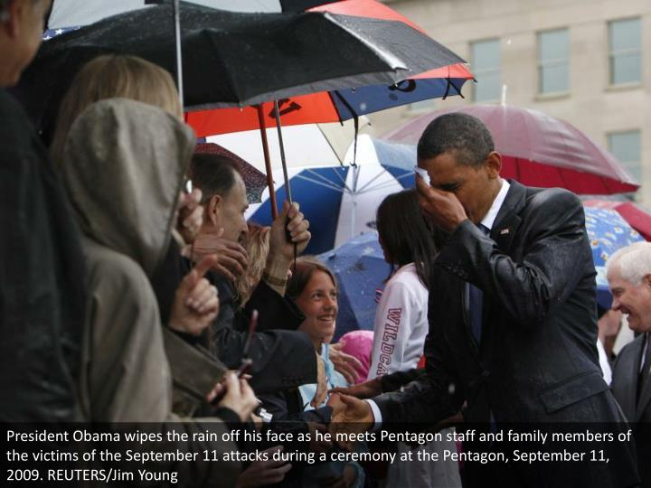 President Obama wipes the rain off his face as he meets Pentagon staff and family members of the victims of the September 11 attacks during a ceremony at the Pentagon, September 11, 2009. REUTERS/Jim Young