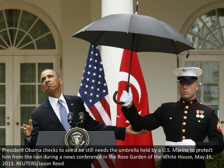 President Obama checks to see if he still needs the umbrella held by a U.S. Marine to protect him from the rain during a news conference in the Rose Garden of the White House, May 16, 2013. REUTERS/Jason Reed
