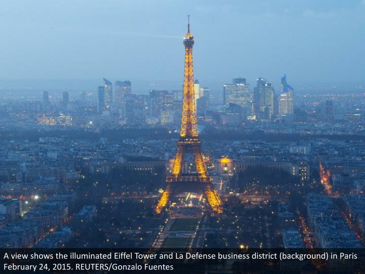 A view shows the illuminated Eiffel Tower and La Defense business district (background) in Paris Feb...