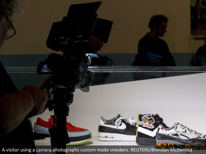 A visitor using a camera photographs custom made sneakers. REUTERS/Brendan McDermid