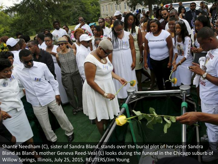 Shante Needham (C), sister of Sandra Bland, stands over the burial plot of her sister Sandra Bland as Bland's mother Geneva Reed-Veal (L) looks during the funeral in the Chicago suburb of Willow Springs, Illinois, July 25, 2015. REUTERS/Jim Young