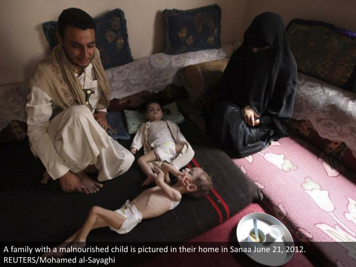 A family with a malnourished child is pictured in their home in Sanaa June 21, 2012. REUTERS/Mohamed al-Sayaghi