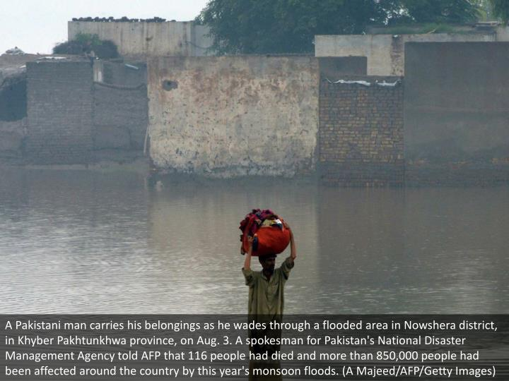 A Pakistani man carries his belongings as he wades through a flooded area in Nowshera district, in Khyber Pakhtunkhwa province, on Aug. 3. A spokesman for Pakistan's National Disaster Management Agency told AFP that 116 people had died and more than 850,000 people had been affected around the country by this year's monsoon floods. (A Majeed/AFP/Getty Images)