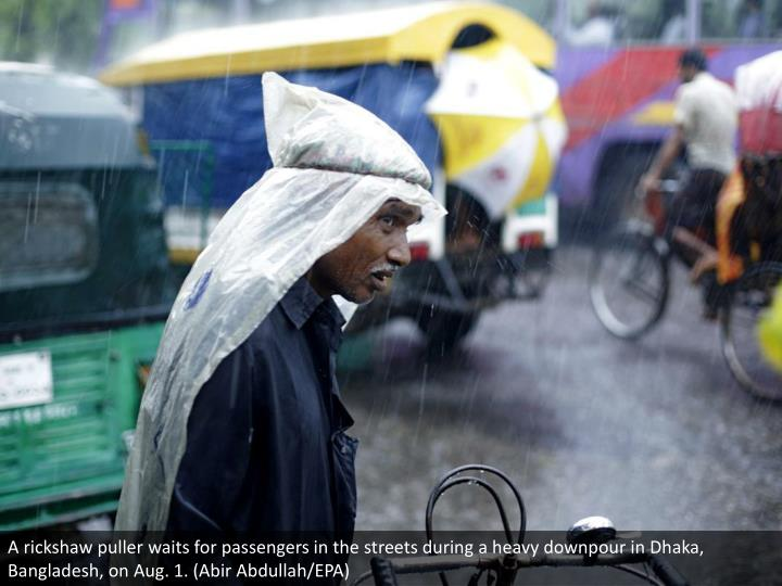 A rickshaw puller waits for passengers in the streets during a heavy downpour in Dhaka, Bangladesh, on Aug. 1. (Abir Abdullah/EPA)