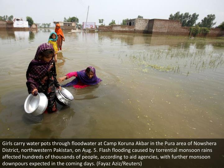 Girls carry water pots through floodwater at Camp Koruna Akbar in the Pura area of Nowshera District, northwestern Pakistan, on Aug. 5. Flash flooding caused by torrential monsoon rains affected hundreds of thousands of people, according to aid agencies, with further monsoon downpours expected in the coming days. (Fayaz Aziz/Reuters)